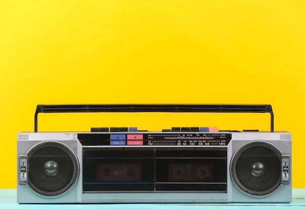 80년대 복고풍의 오래된 휴대용 스테레오 라디오 카세트 레코더가 노란색 배경에 있습니다.