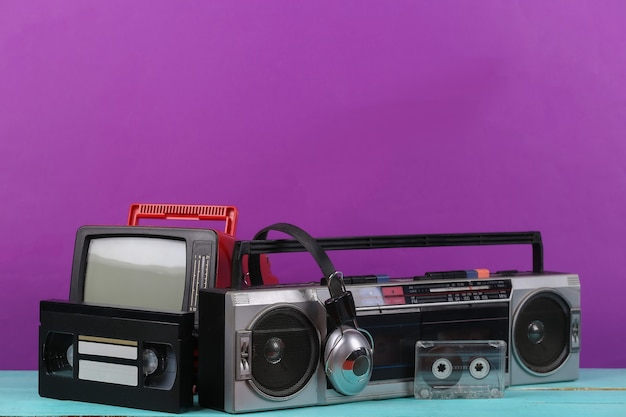 80년대 복고풍의 구식 휴대용 스테레오 라디오 카세트 레코더, tv 세트, 헤드폰, 보라색 배경의 오디오 및 비디오 카세트. 속성 80년대, 레트로 미디어, 엔터테인먼트