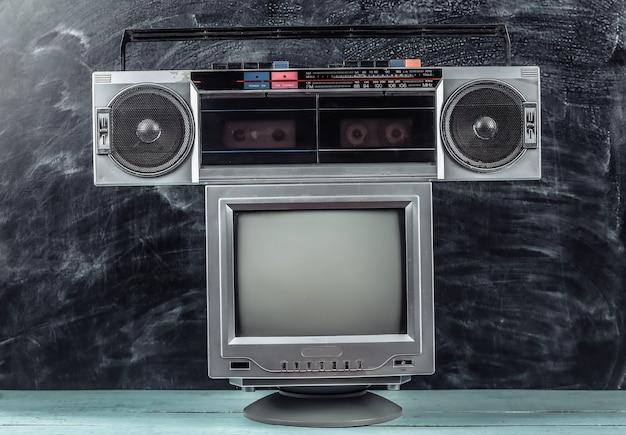 80年代のレトロな時代遅れのポータブルステレオラジオカセットレコーダー、黒板の背景にテレビセット
