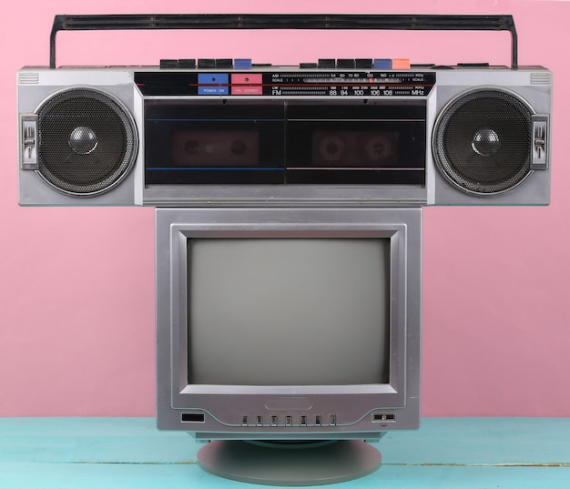 80년대 복고풍의 구식 휴대용 스테레오 라디오 카세트 레코더, 분홍색 배경의 tv. 속성 80년대, 레트로 미디어, 엔터테인먼트
