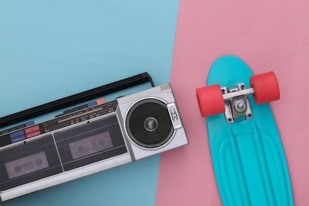 80년대 복고풍의 구식 휴대용 스테레오 라디오 카세트 레코더, 분홍색 파란색 배경에 크루저 보드가 있습니다. 평면도. 플랫 레이
