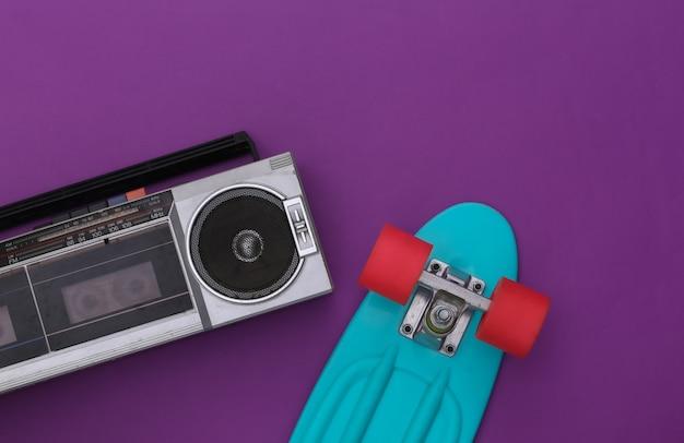 보라색 배경에 크루저 보드가 있는 80년대 복고풍의 구식 휴대용 스테레오 라디오 카세트 레코더. 평면도. 플랫 레이