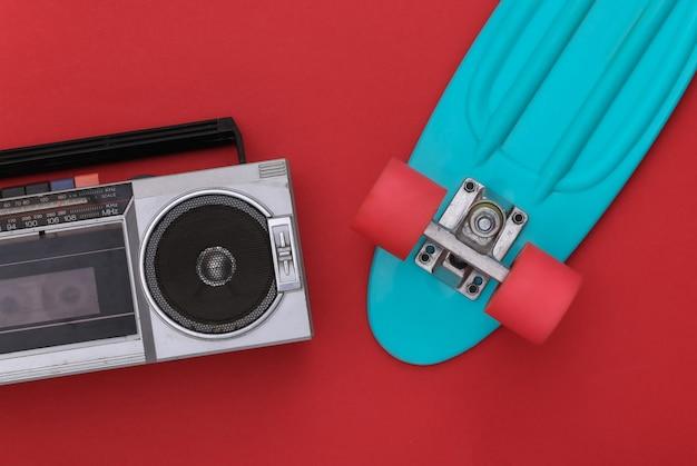 빨간색 배경에 크루저 보드가 있는 80년대 복고풍의 구식 휴대용 스테레오 라디오 카세트 레코더. 평면도. 플랫 레이
