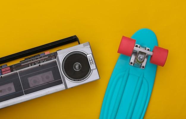 노란색 배경에 크루저 보드가 있는 80년대 복고풍의 구식 휴대용 스테레오 라디오 카세트 레코더. 평면도. 플랫 레이
