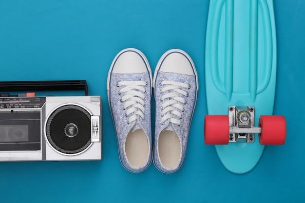 80년대 복고풍의 구식 휴대용 스테레오 라디오 카세트 레코더, 크루저 보드, 파란색 배경 운동화. 평면도. 플랫 레이