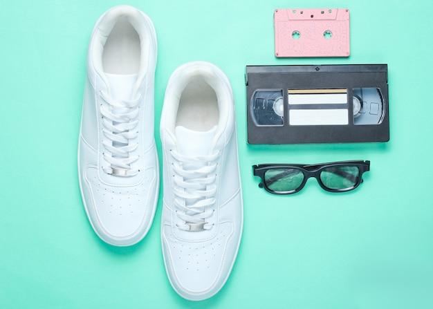 80年代、レトロなスタイル。ホワイトヒップスタースニーカー、オーディオおよびビデオカセット