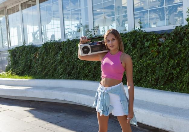 屋外の明るい晴れた日にラジカセオーディオテープレコーダーとオーディオカセットを持つ若い魅力的な女性の80年代スタイルの画像