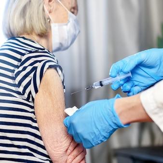 85 세 여성이 의사로부터 covid-19 백신을 접종받습니다. 노인 예방 접종