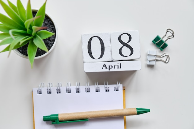 Дата на белых деревянных кубиках - восьмое, 8 апреля на белом столе. вид сверху.