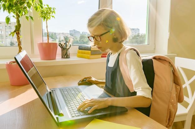 8歳の小さな学生少女はラップトップを使う