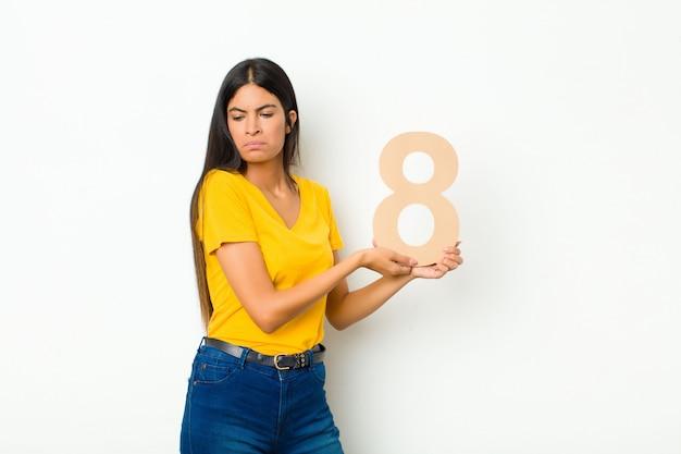 Грустный, подавленный, несчастный, держит номер 8.