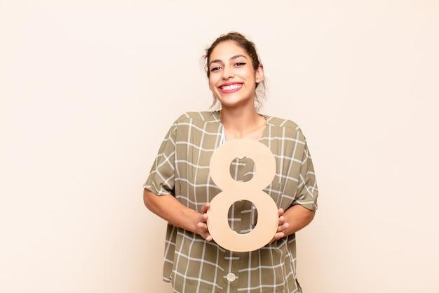 Взволнован, счастлив, радостен, держит номер 8.