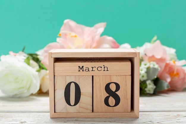 Деревянные блоки в коробке с датой, днем и месяцем 8 марта. календарь деревянных блоков