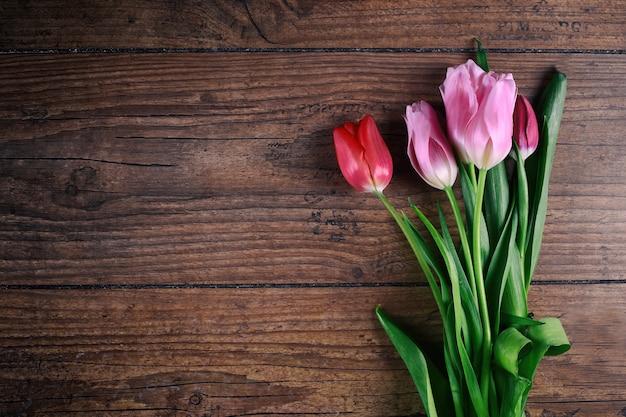 Розовые тюльпаны цветы на деревенском столе на 8 марта, международный женский день, день рождения, день святого валентина или день матери - вид сверху