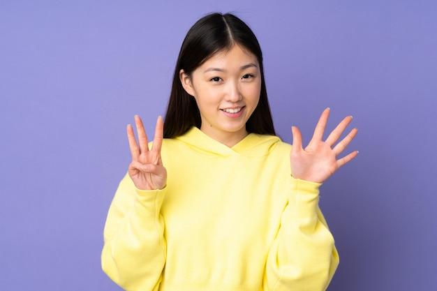 Молодая азиатская женщина изолированная на фиолетовом космосе подсчитывая 8 с пальцами