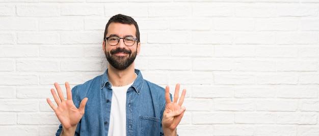 指で8を数える白いレンガの壁の上のひげを持つハンサムな男