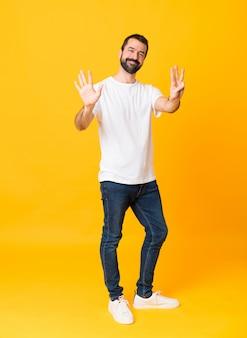 指で8を数える孤立した黄色の背景上のひげを持つ男の全身ショット