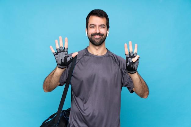 指で8を数える孤立した青い壁の上のひげを持つ若いスポーツ男