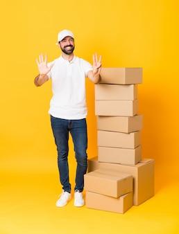 指で8を数える孤立した黄色の背景上のボックスの間で配達人の全身ショット