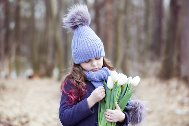 Милая маленькая девочка в парке с букетом белых тюльпанов. цветы в подарок женскому дню матери. 8 марта. пасха. девушка с букетом на счастливый день матерей. делает подарок для твоей мамы.