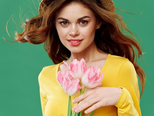 Женщина в красивом платье с цветами на 8 марта, подарки цветы на светлом фоне ко дню святого валентина студия