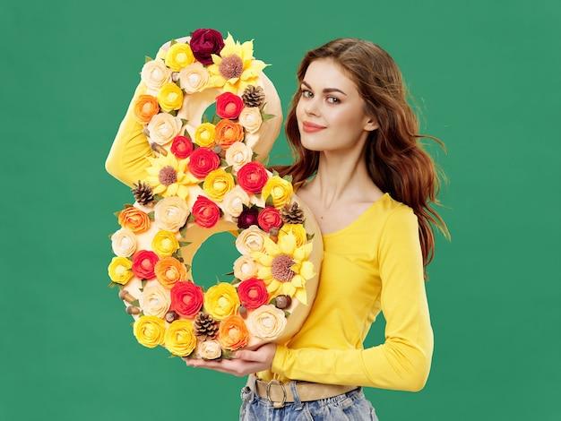 Женщина в красивом платье с цветами на 8 марта дарит цветы светлой поверхности ко дню святого валентина студии
