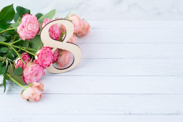 Деревянная фигура 8 с розовыми цветами на белом столе. международный женский день. восьмое марта