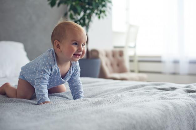 自宅のベッドの上でクロール生後8ヶ月の幸せな男の子