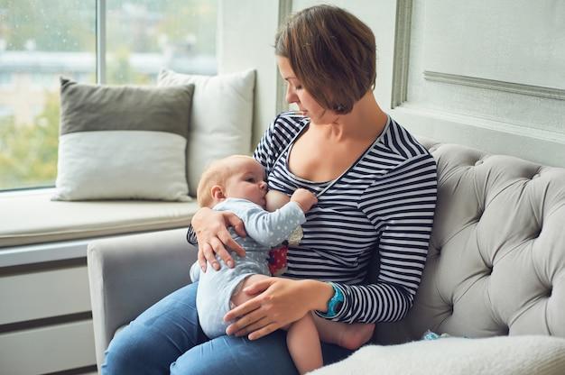 生後8か月の赤ちゃんが母乳を食べる。母乳育児幼児男の子、家の内部のソファーに立地