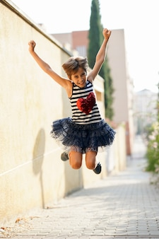 小さな女の子、8歳、屋外ジャンプします。