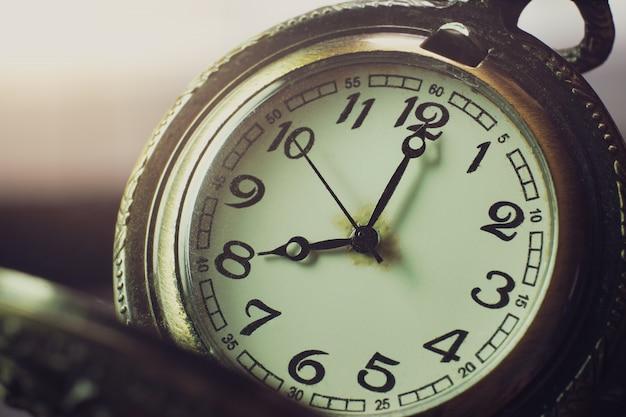 テーブルと日光のクローズアップの懐中時計。午前8時。朝の時間。今日から仕事を始めるというコンセプト。