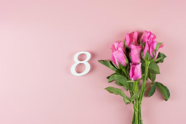 ピンクのバラの花とテキストのコピースペースを持つ8番目の数。愛、平等、国際的な女性の日のコンセプト