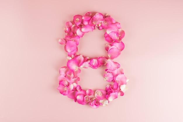 テキストのコピースペースを持つピンクのバラの花びらの8番目の数の形状。愛、平等、国際的な女性の日のコンセプト