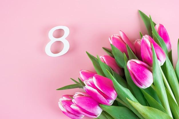 ピンクのチューリップの花とテキストのコピースペースを持つ8番目の数。愛、平等、国際的な女性の日のコンセプト