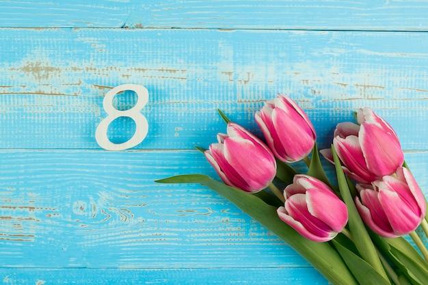 ピンクのチューリップの花とテキストのコピースペースを持つ青い木製テーブル背景に8番目の数。愛、平等、国際的な女性の日のコンセプト
