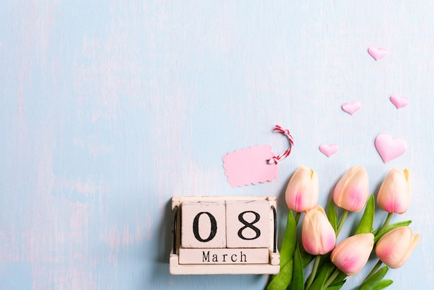 Концепция международного женского дня. розовые тюльпаны и бумажные сердечки с текстом 8 марта