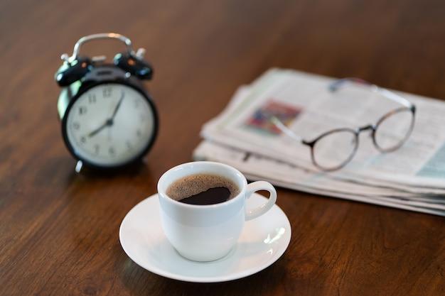 朝の8時のホットコーヒーカップとビンテージの時計時間