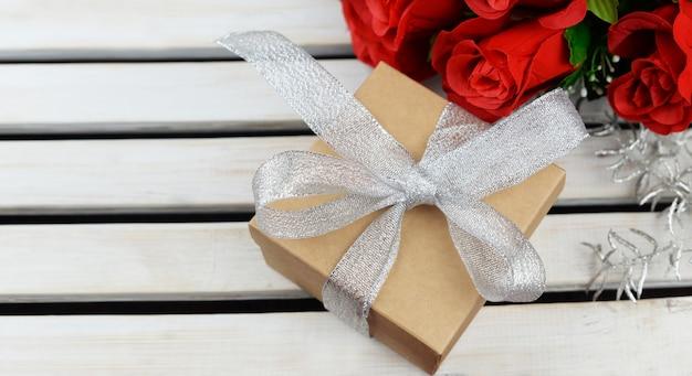 Подарочная коробка с бантом с цветами красных роз на праздник день святого валентина 8 марта день матери на деревянном фоне