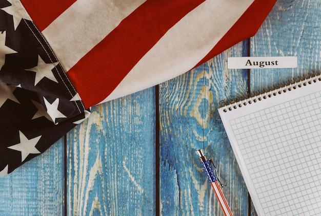 カレンダー年の8月月アメリカ合衆国のメモ帳とオフィスの木製テーブルにペンで自由と民主主義のシンボルのアメリカ合衆国の旗