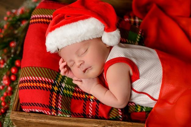 クリスマスのスーツで生後8日の小さな新生児の女の子