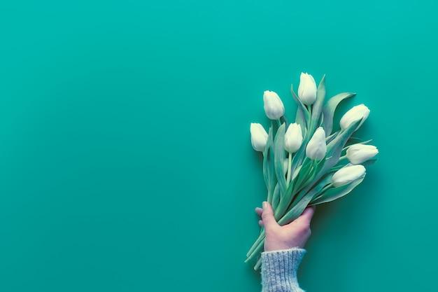 Женщина рука держать букет из белых тюльпанов, мята зеленая бумага. весна плоская планировка, вид сверху с копией пространства, пространство для текста. день матери, международный женский день 8 марта, день рождения, юбилей приветствие фон.