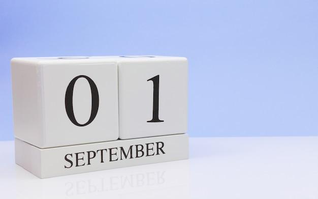 9月1日月の1日目、反射と白いテーブルの上の毎日のカレンダー