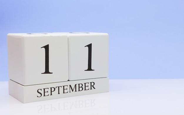 9月11日月の11日目、反射と白いテーブルに毎日のカレンダー