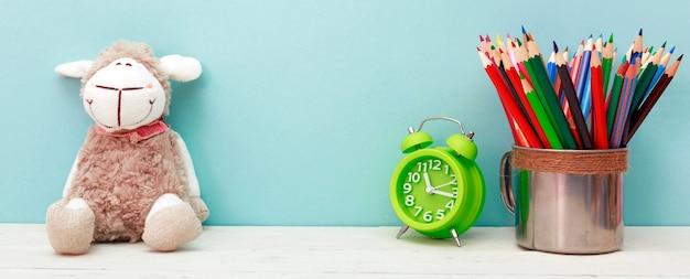 9月1日のコンセプト。白い木製の背景に緑の目覚まし時計、カップ、色鉛筆。学校のコンセプトに戻る。
