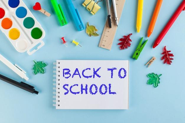 青い表面に学校の文房具。学校に戻るレタリング。ナレッジデーのコンセプト、9月1日。