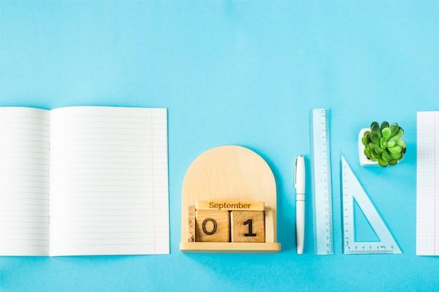 青色の背景に研究用の物資の中で木製のカレンダーに9月1日