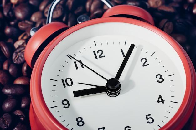 コーヒー豆の上に横たわる赤い目覚まし時計。時計の9時7分。