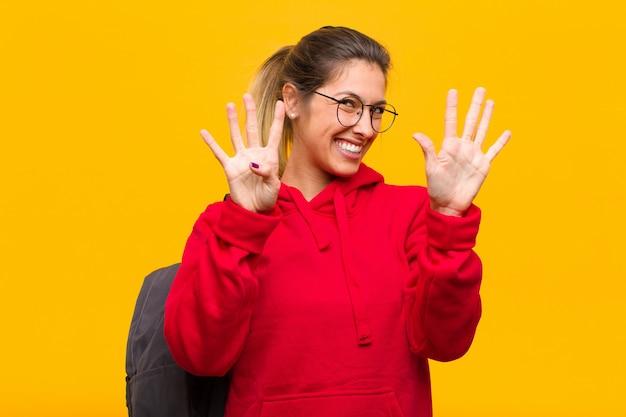 若い可愛い学生笑顔とフレンドリーな探して、9または9番目の手を前方に表示して、カウントダウン