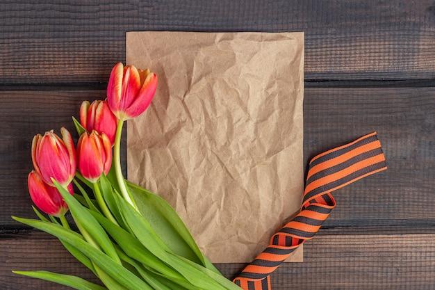 9 мая фон - шаблон пустой поздравительной открытки с красными тюльпанами, георгиевская лента и бумажные записки на деревянном фоне. день победы или день защитника отечества концепции. вид сверху, скопируйте пространство для текста
