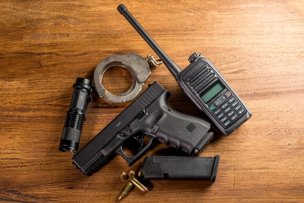9 mm pistol gun and bullets strewn with ammunition on wooden background